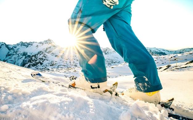 Las piernas del esquiador profesional al atardecer en un momento de relax en la estación de esquí de los alpes franceses