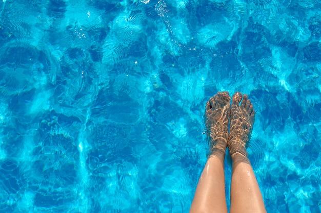 Piernas femeninas en el agua de la piscina en verano