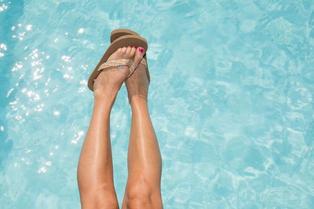 Piernas femeninas bronceadas en la piscina
