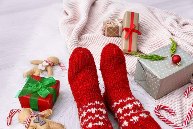 Piernas femeninas en calcetines calientes, regalos de navidad y cuadros sobre fondo claro