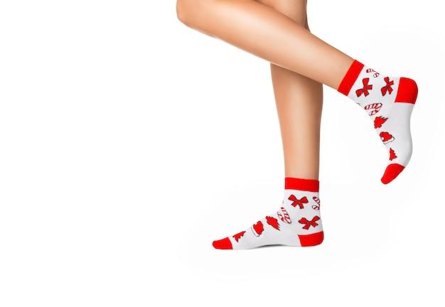 Piernas femeninas en calcetines de navidad sobre un fondo blanco.