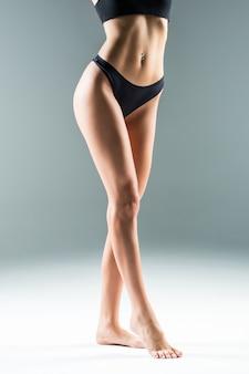 Piernas femeninas delgadas y sexy aisladas en la pared gris