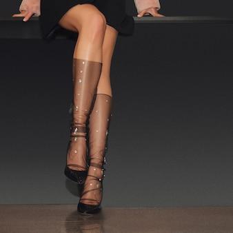 Piernas femeninas desnudas en calcetines hasta la rodilla y zapatos de tacón alto.