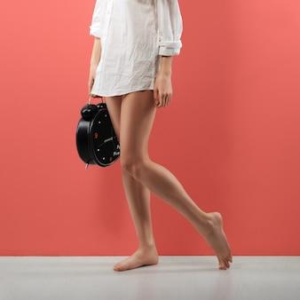 Piernas femeninas desnudas, camisa de hombre blanca y enorme reloj despertador en la mano