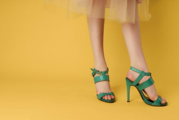 Piernas femeninas en fase de zapatos verdes estilo de verano fondo amarillo