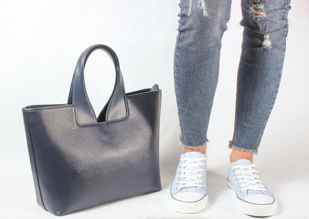 Piernas femeninas en jeans y zapatillas posando con una bolsa en blanco