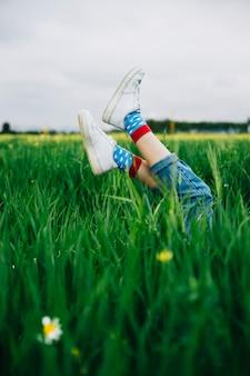 Piernas femeninas jugando en el aire en la hierba verde