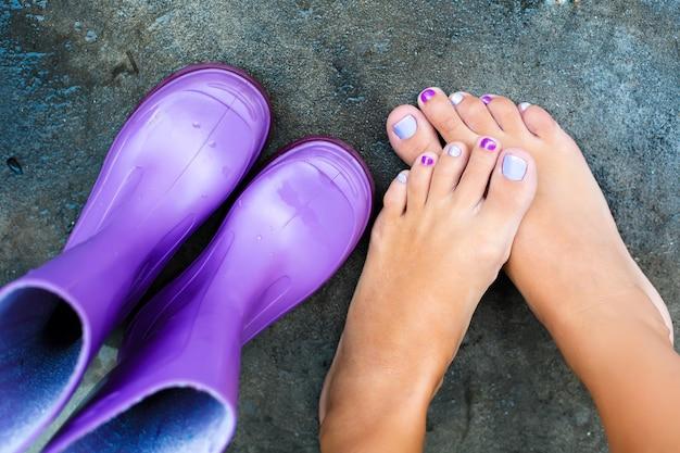 Piernas femeninas junto a botas de colores para un día lluvioso