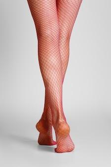 Piernas femeninas largas y musculosas en medias de rejilla rosa sexy. vista trasera.