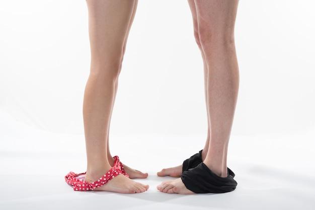 Piernas femeninas y masculinas quitándose la ropa interior. pareja de enamorados de pie juntos.