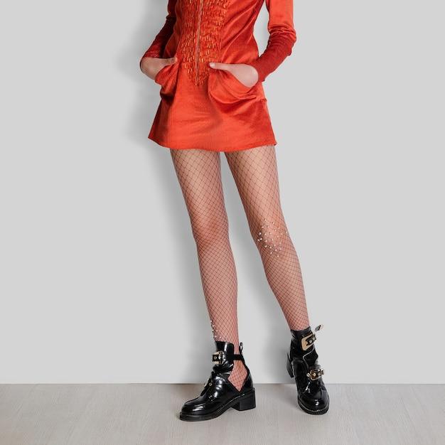 Piernas femeninas en medias de rejilla, vestido rojo y