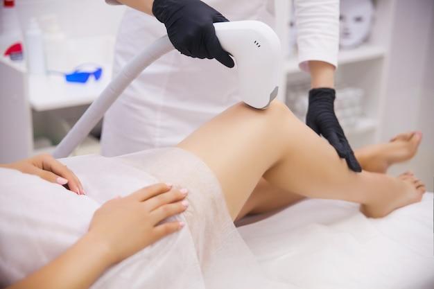 Piernas femeninas, mujer en clínica de belleza profesional durante la depilación láser