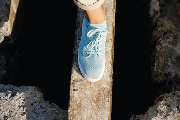 Piernas femeninas en pantalones beige y zapatillas de deporte en el tablero sobre el acantilado