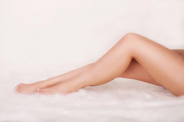 Piernas femeninas perfectas aisladas en blanco