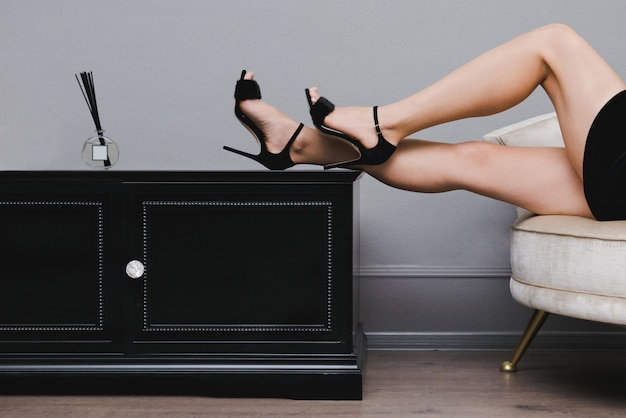 Piernas femeninas perfectas. sandalias negras con pelaje con tacones altos.