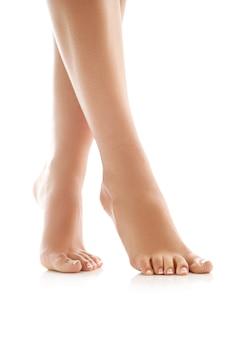 Piernas femeninas y pies descalzos. concepto de cuidado de la piel y pedicura.