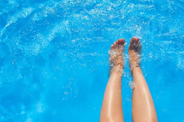 Piernas femeninas en piscina de agua azul