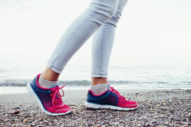 Las piernas femeninas en zapatillas de deporte rosadas y azules y los pantalones vaqueros están en la playa