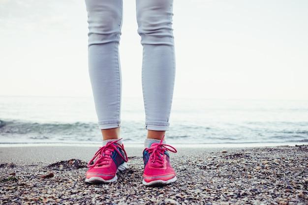 Piernas femeninas en las zapatillas de deporte rosadas que se colocan en la playa cerca del agua por la tarde