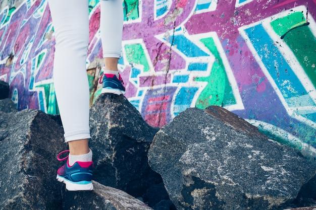 Piernas femeninas en zapatillas y jeans trepan sobre las rocas en la superficie de una pared de graffiti