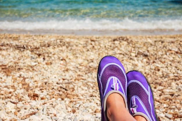 Piernas femeninas con zapatos de neopreno de natación.