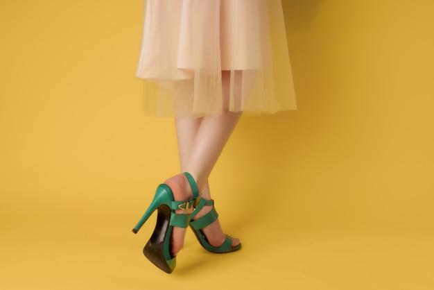 Piernas femeninas, zapatos verdes, estilo veraniego, fondo amarillo. foto de alta calidad