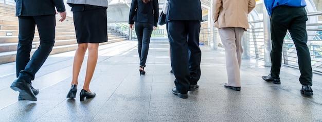 Piernas de gente de negocios caminando en la ciudad moderna.