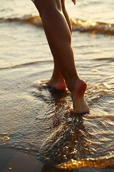 Piernas de hermosa mujer en la playa