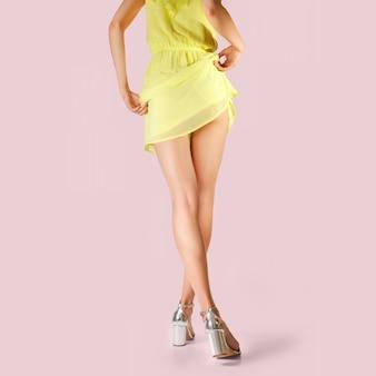 Piernas de hermosa niña con vestido corto levantado. foto con trazado de recorte.