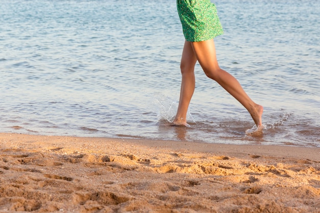 Piernas hermosas de la muchacha que se ejecutan en la playa. linda chica caminando sobre el agua