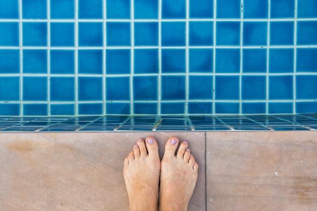 Piernas hermosas de la mujer en piscina.