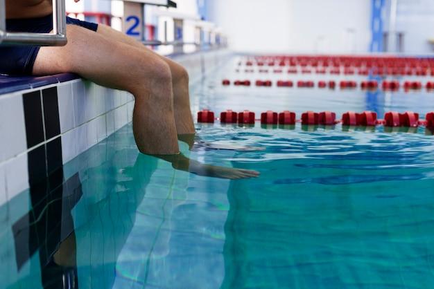 Piernas de hombre entrando en el agua de la piscina