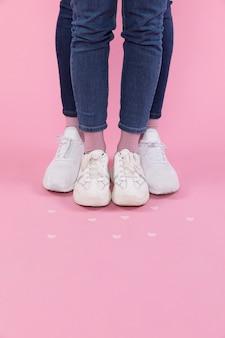 Piernas de hombre y mujer en jeans y zapatillas cerca de corazones decorativos