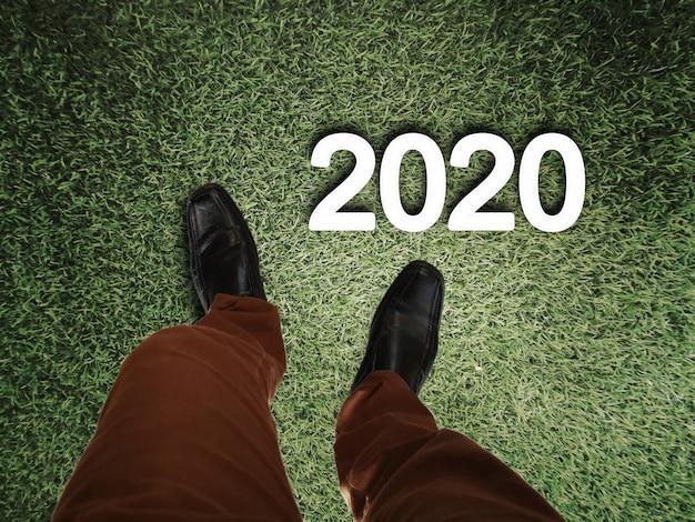Piernas de hombre de negocios de pie en el piso de hierba con 2020