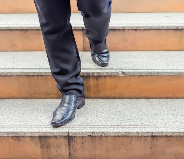 Piernas del hombre de negocios que toman el paso en un nivel inferior en una escalera - concepto de decisión de inversión de negocios mal