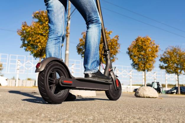 Piernas de un hombre parado en e-scooter estacionado en la acera en el paisaje urbano en la puesta de sol. transporte urbano de moda en scooter eléctrico moderno. concepto de movilidad ecológica.