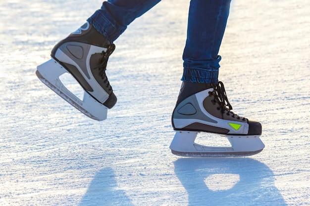Piernas de un hombre patinando sobre una pista de hielo