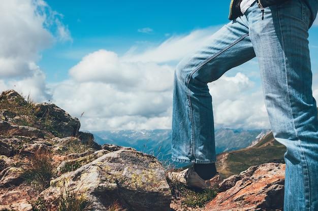 Piernas de hombre de pie en la cima del acantilado