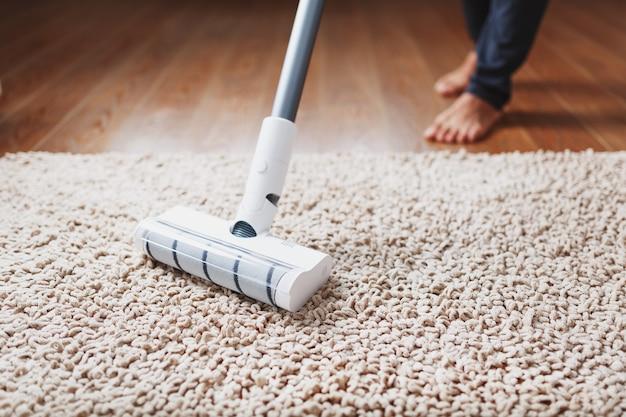 Piernas humanas y un cepillo turbo blanco de una aspiradora inalámbrica limpian la alfombra de la casa. tecnologías modernas para la limpieza.