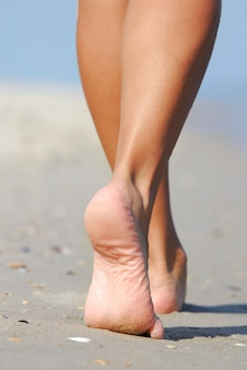 Piernas humanas. hermosa mujer caminando por la playa