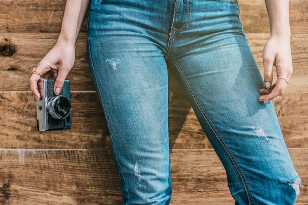 Piernas de jeans mujer recortada con cámara antigua vintage