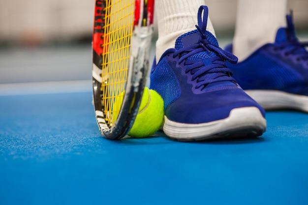 Piernas de joven en una cancha de tenis cerrada con pelota y raqueta