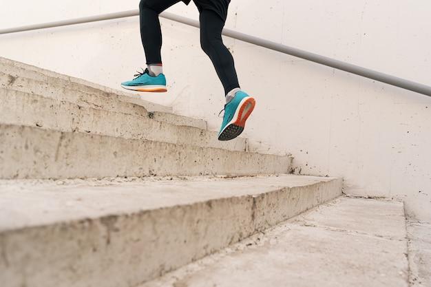 Piernas de joven haciendo ejercicios de intervalo en las escaleras