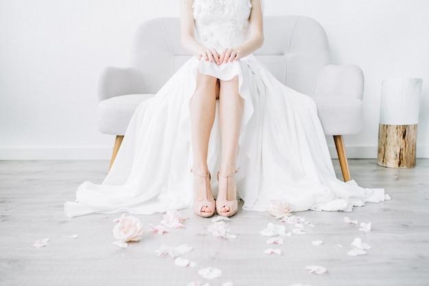 Piernas de la joven novia en zapatos de tacón de color rosa y pétalos de flores rosas
