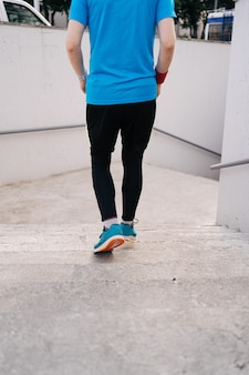 Piernas de joven practicando entrenamiento de intervalo en las escaleras