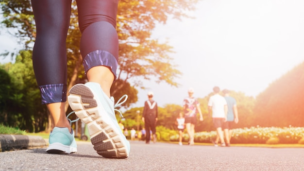 Las piernas jovenes de la mujer de la aptitud que caminan con el grupo de personas ejercitan caminar
