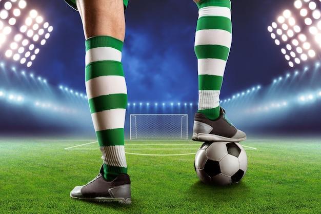 Piernas de jugador de fútbol con una pelota de pie en el campo de fútbol