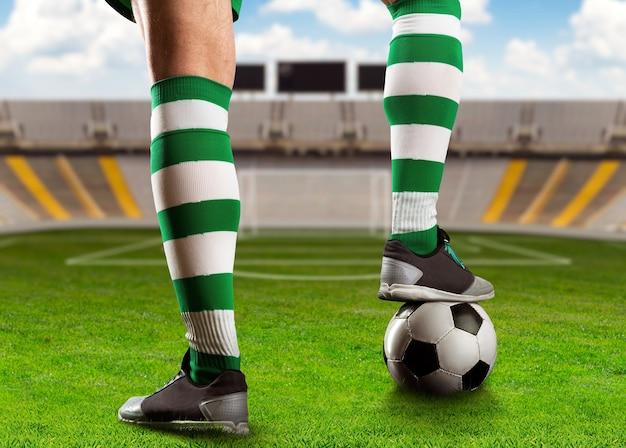 Piernas de jugador de fútbol con una pelota de pie en el estadio de fútbol