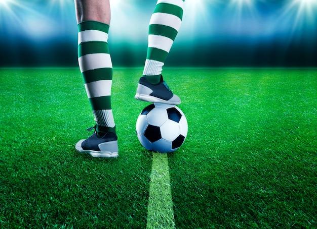 Piernas de jugador de fútbol con una pelota de pie en el estadio