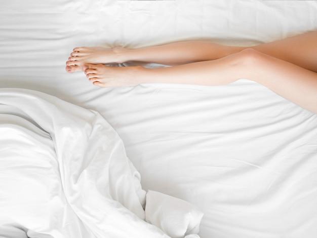 Piernas largas y delgadas femeninas en las sábanas blancas. ciérrese para arriba de hembra con la piel sana perfecta de las piernas sedosas después de la depilación en la cama blanca en interior ligero. belleza, concepto de cuidado de la piel.
